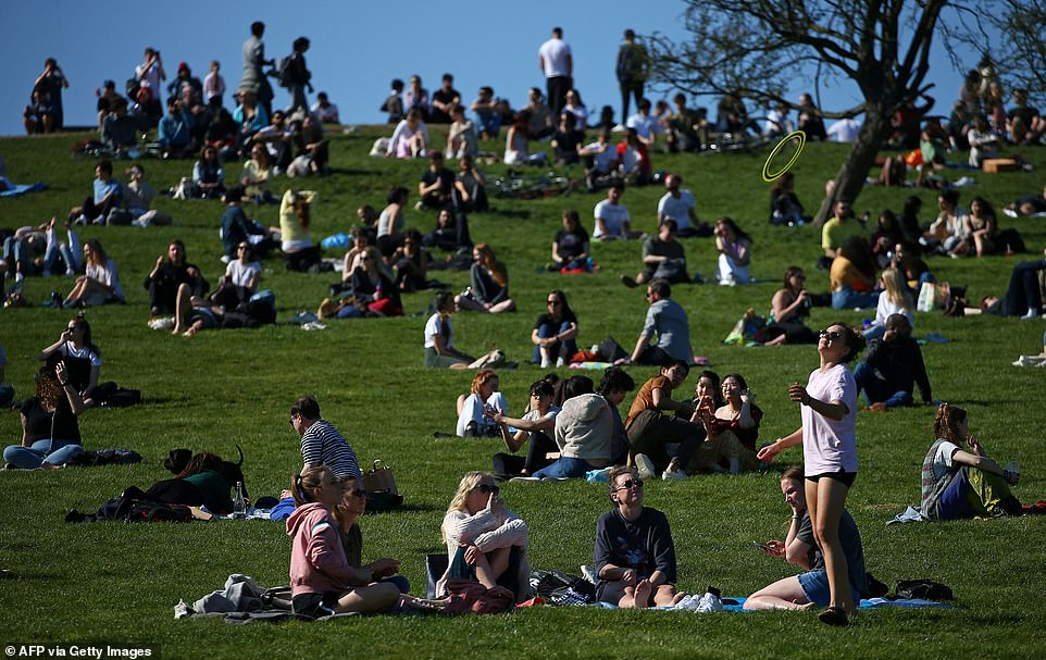 Groups of people sit and chat together in the warm weather on Primrose Hill in London this afternoon as the rule of six was reintroduced
