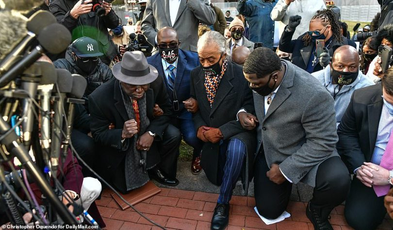 Floyd's brother Philonise took a knee in front of Hennepin County Courthouse on Monday morning for 8 minutes and 46 seconds – the length of time Chauvin knelt on the black man's neck last spring. From left: Floyd family attorney Ben Crump, Philonise, the Rev Al Sharpton, Floyd's nephew Brandon Williams