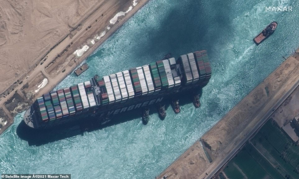 Although the ship is free, it is unclear how long it will take to deal with the backlog its grounding caused. Pictured: A satellite image shows the tugboats alongside the Ever Given on Monday
