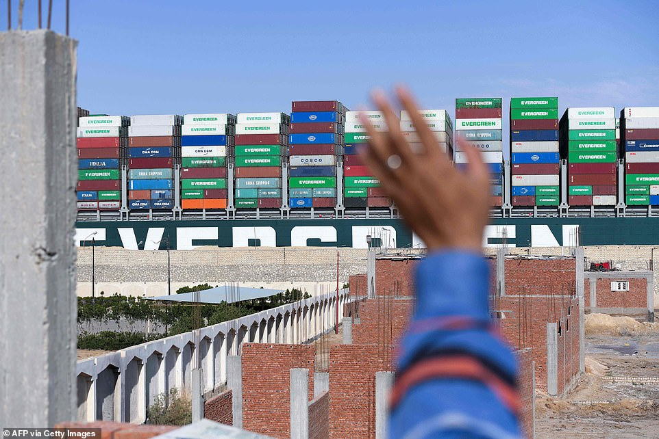A man waves goodbye to the Ever Given on Monday as economists said its disruption of shipping through the Suez Canal probably won't have an impact on global trade for more than a few weeks