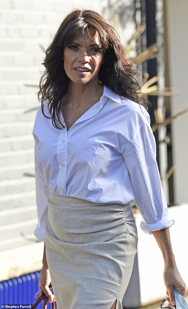 Stylish: The radio host, 52, looked effortlessly chic in a white oversized shirt and beige high waisted pencil skirt with a large slit above the knee
