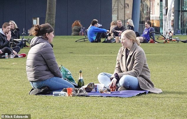 Two friends enjoying a drink in Potter's Fields Park near Tower Bridge yesterday amid barmy temperatures for this time of the year