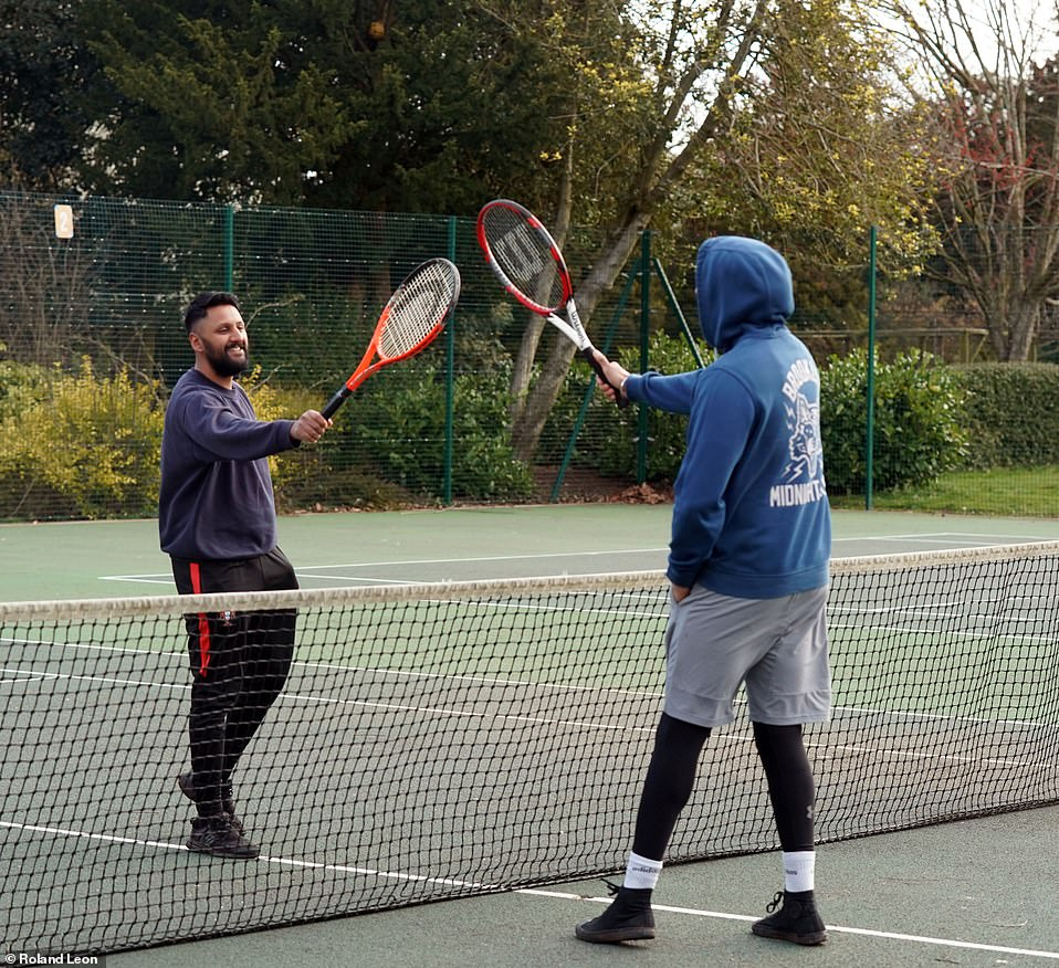 Two tennis players touch rackets over the net at Cannon Hill Park in Birmingham today as outdoor sport was given the go ahead