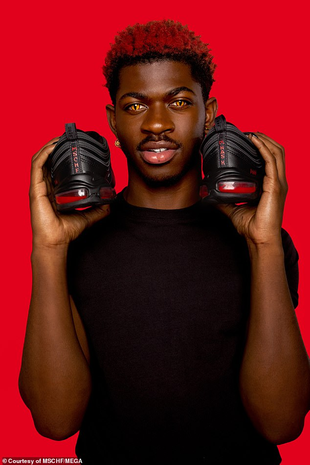 Musician Lil Nas X poses with his custom Satan Shoes by MSCHF, which sold out all 666 available pairs almost immediately after their release Monday -
