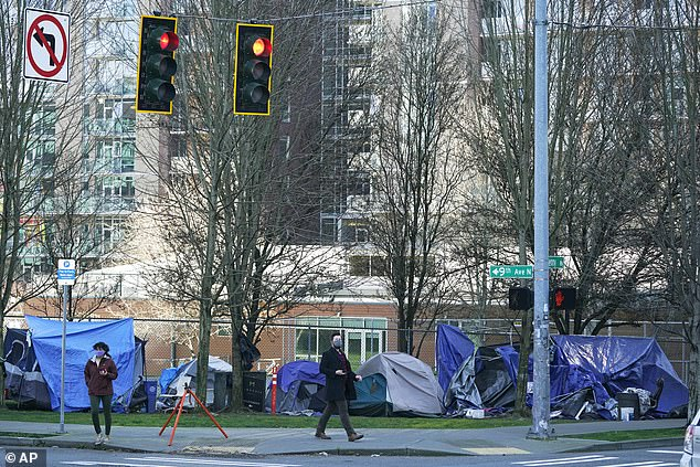With apartment buildings in the background, pedestrians walk past tents used by people lacking housing at Denny Park in Seattle on March 3