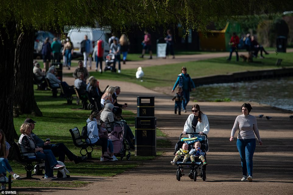 People enjoy the sunshine at Stratford-upon-Avon in Warwickshire today as they go for a walk through a park