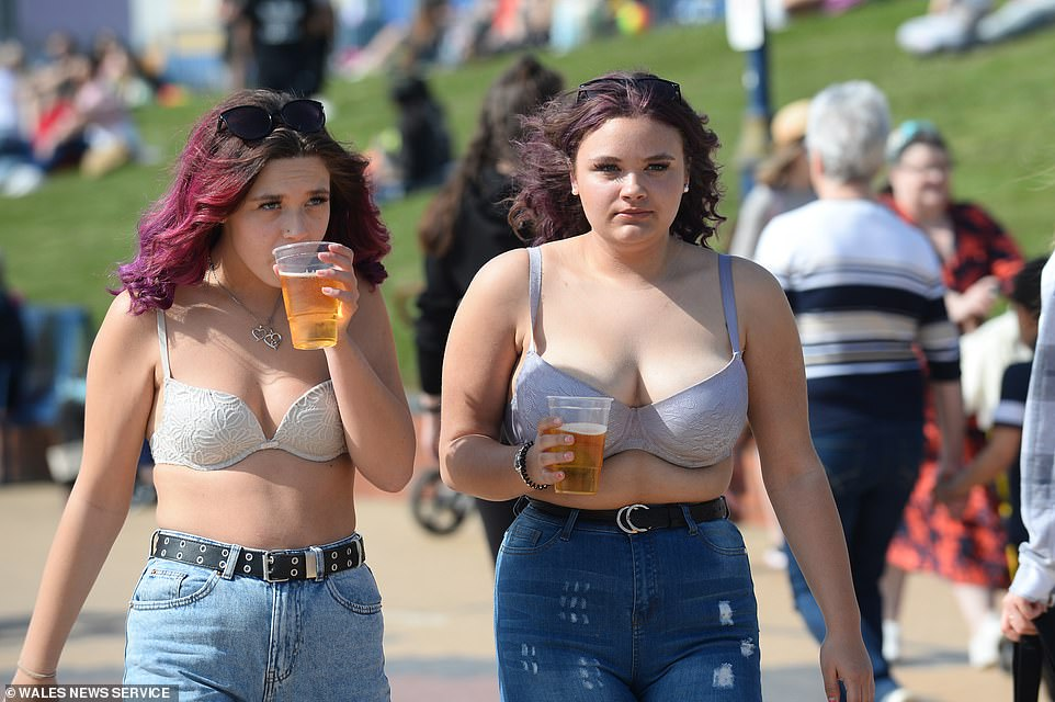 Two women enjoy a drink as they walk along the promenade at Barry Island beach in South Wales this afternoon
