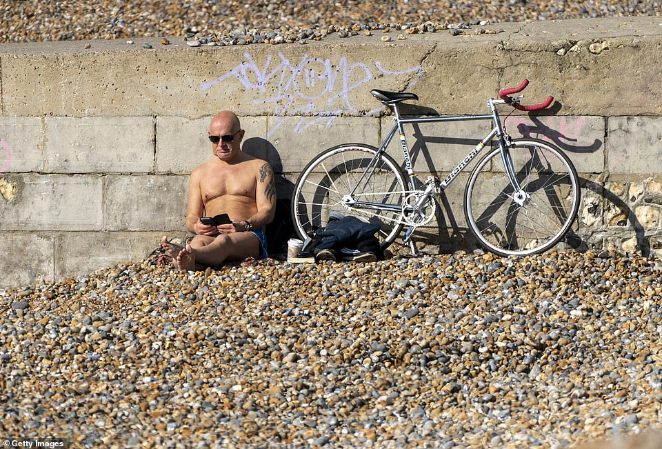 A man takes advantage of the unseasonably warm weather and relaxing of lockdown restrictions at Brighton beach today