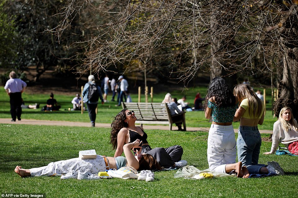 People enjoy the sunshine at St James's Park in London today as the capital has warm weather conditions