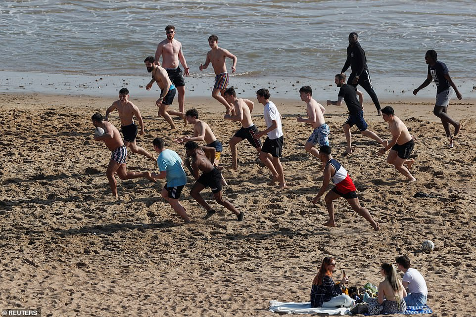 People play rugby as they enjoy the hot weather at Bournemouth Beach on the Dorset coast this afternoon