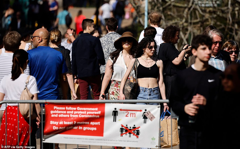 People walk in the sunshine past a banner asking people to observe the social distancing guidelines in St James's Park today