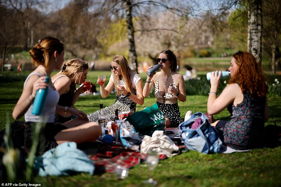 A group of women enjoy the sunshine at St James's Park in London this afternoon