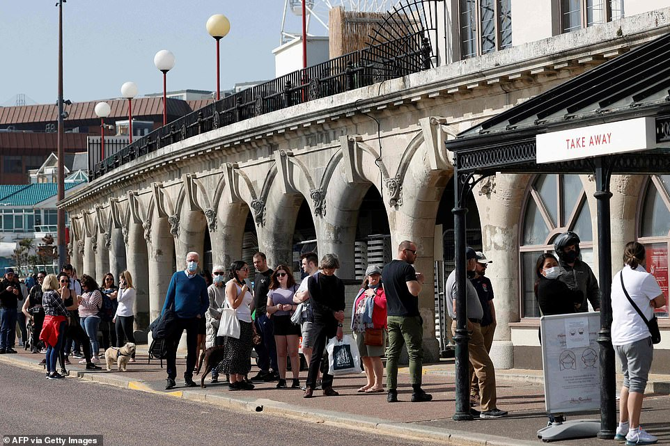 Members of the public queue for food in Bournemouth today as people make the most of the warmth