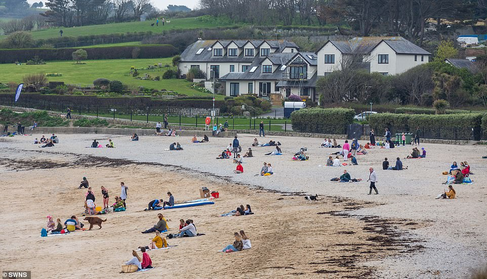 People make the most of good weather at Falmouth in Cornwall this afternoon where non-locals are urged to stay away