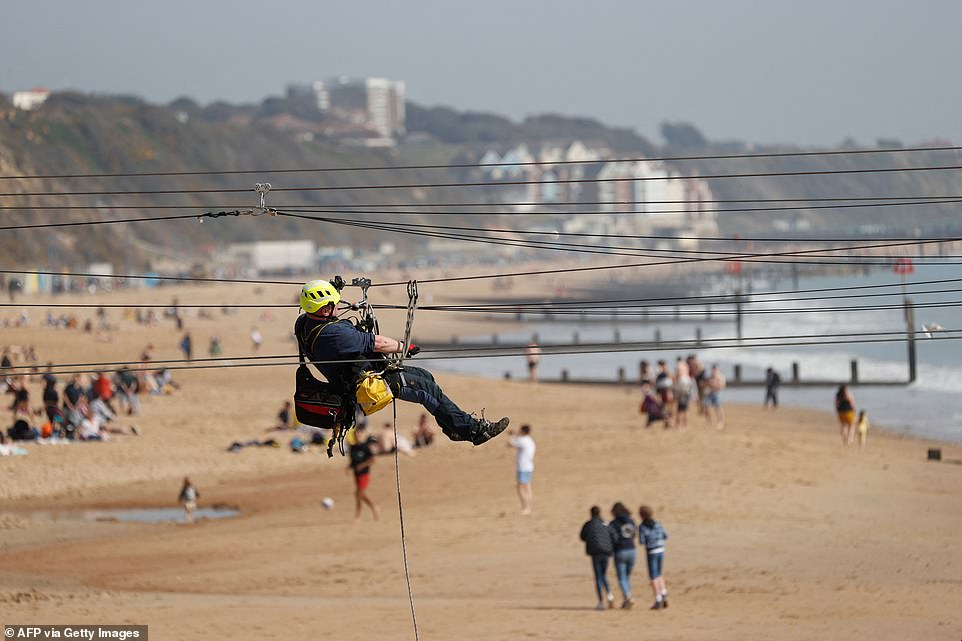 A contractor checks a zip line by the beach in Bournemouth today as a spell of warm weather covers the South of England