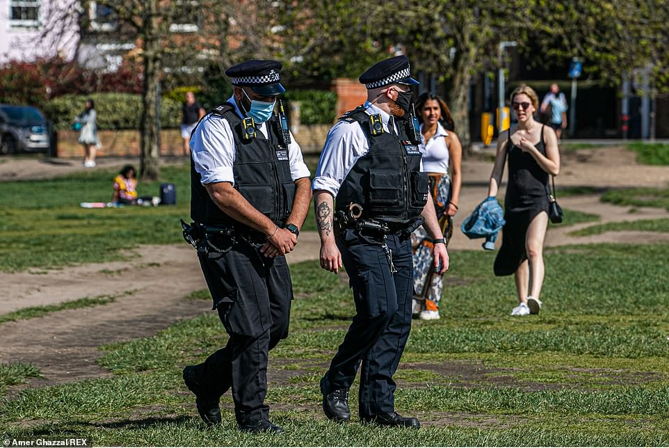 Police officers walk among the crowds as the warm spring sunshine encourages people out to Wimbledon Common today