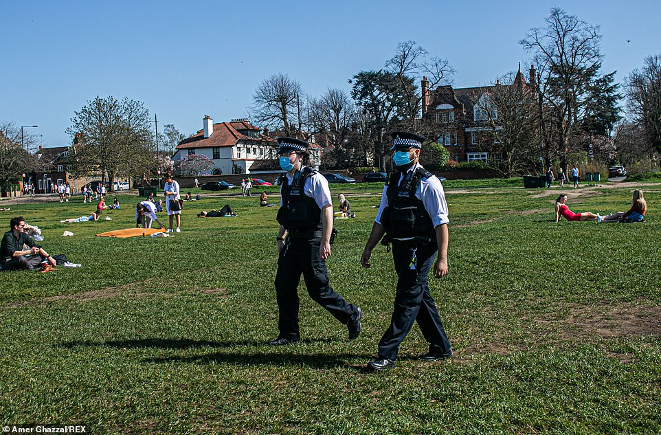 Police officers walk through Wimbledon Common today as the warm sunshine has encouraged people to meet outdoors