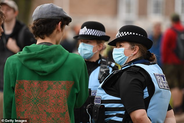 A demonstrator talks with police officers during a 'Kill the Bill' protest in Bristol this evening