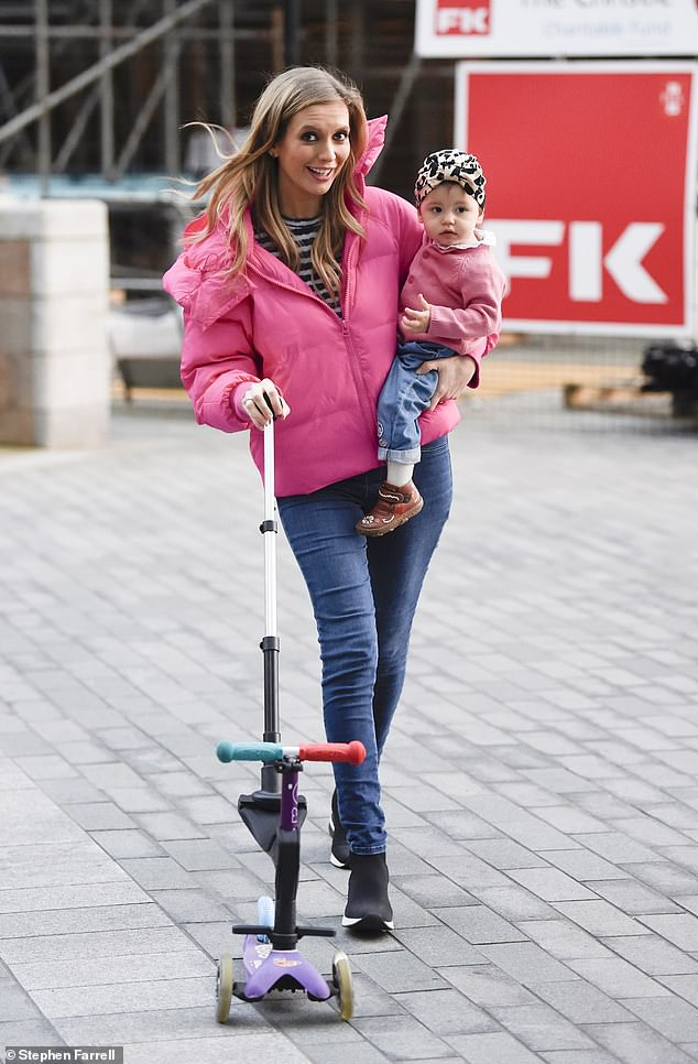Good spirits: The mother-of-one styled her golden locks in loose waves and cut a casual figure as she pushed her daughter's scooter