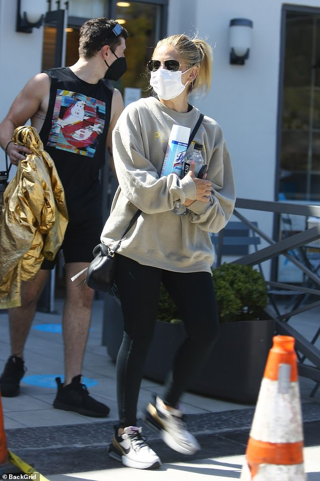 Safety first:Clearly taking note of the severity of the coronavirus, Sarah wore a white face mask and carried a can of Lysol disinfectant spray