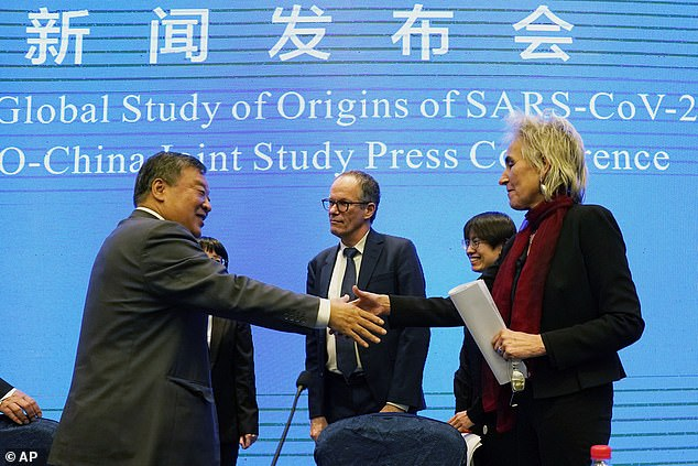 More than 420 days have passed since the World Health Organisation declared that a strange new disease killing people in a central Chinese city was sufficiently alarming to be declared a global health emergency. Pictured: Marion Koopmans, right, and Peter Ben Embarek, center, of the World Health Organization team with Chinese counterpart Liang Wannian