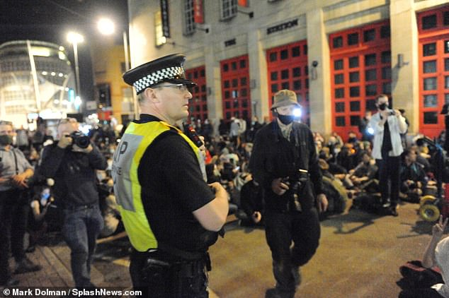 A police officer is seen on standby as protestors march to Bridewell Police station for a sit-down protest on Tuesday evening