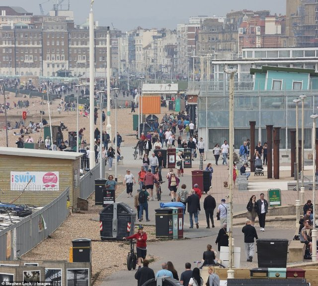 People walk along the promenade at Brighton this afternoon as sunseekers head to the East Sussex coast