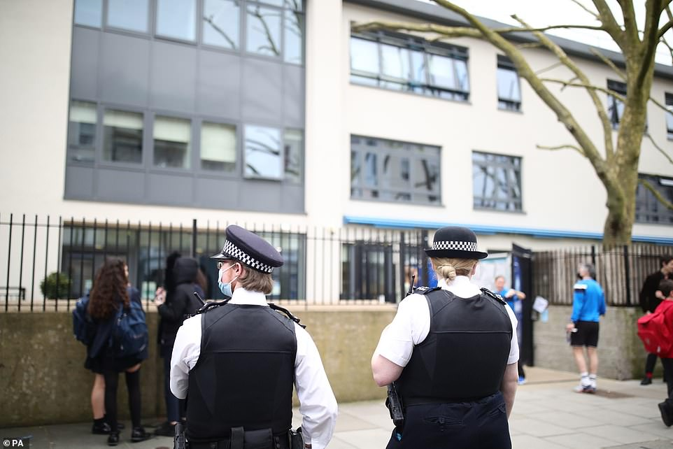 Officers stand outside the gates of the school on Wednesday morning during the demonstration