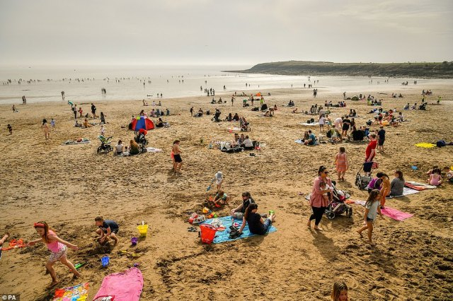 People on the beach at Barry Island in South Wales as the UK enjoys unseasonably warm temperatures