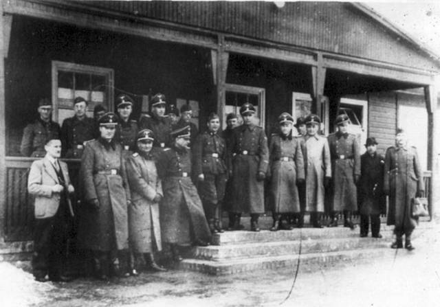 A chilling black-and-white photograph of smiling SS officers in front of a wooden building offers a glimpse into one of WWII's lesser-known horrors. With its roomy porch and large windows, the building provided a welcome retreat for German soldiers stationed at the infamous Auschwitz-Birkenau death camp, but for inmates, it was a site of degradation and despair