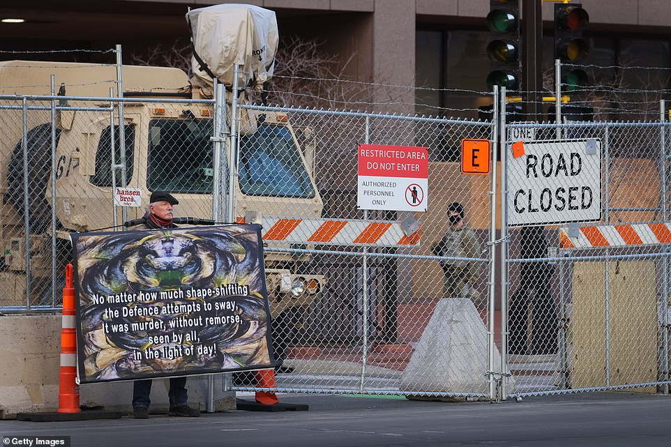 A protester stands near the heavily-fortified courthouse on Wednesday as Chauvin's murder trial resumed