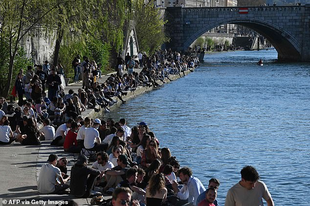 People gather on the Saone river banks in Lyon on March 31, 2021, before the start of the daily curfew aimed at curbing the spread of the Covid-19