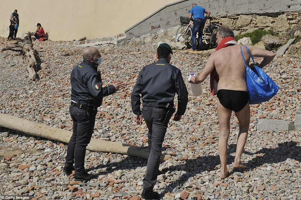 ITALY: Policeman escort a sunbather off the beach in Livorno, Tuscany, after the province was plunged into tough 'red zone' lockdown restrictions amid a third wave of Covid-19
