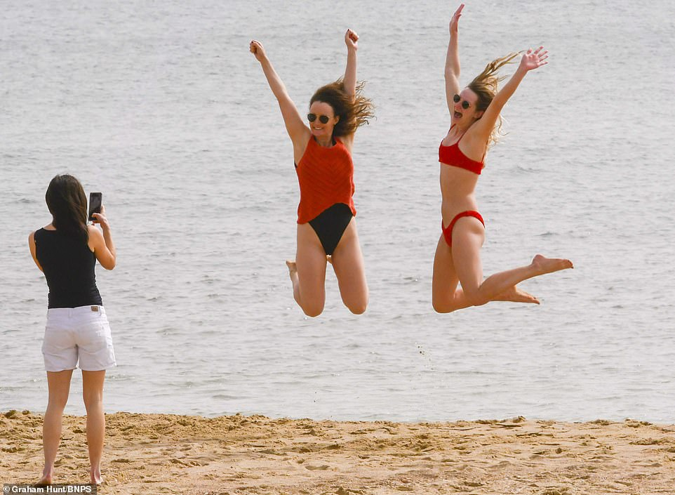 Two women leap in the air as they pose for a photograph from a friend as they enjoy the last day of warm temperatures today in Bournemouth