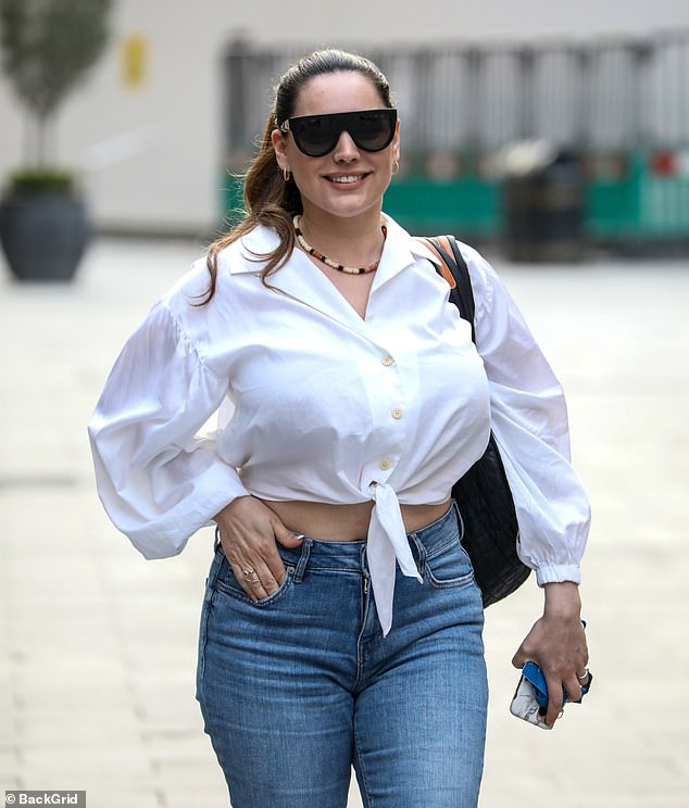 Stylish:The model offered a glimpse of her toned tummy in a knotted white shirt and cropped jeans as she arrived at Global Studios in London to host her drivetime show