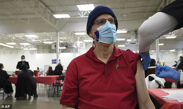 Infectious disease specialists tell DailyMail.com that side effects from coronavirus vaccines are normal and that reports of severe reactions are rare. Pictured:Jeff Klingberg gets a COVID-19 vaccine in Batavia, Illinois, March 19