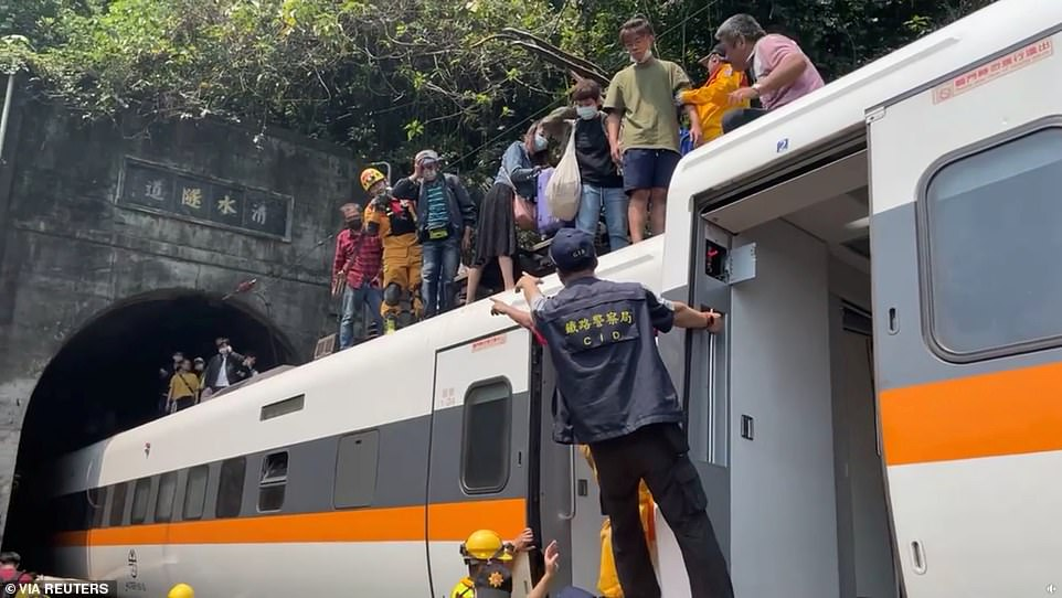 Passengers escape over the roof of the train which was crowded with people for the weekend. Many of those who were seated in the rear carriages were able to climb out and onto the roof to get out unharmed