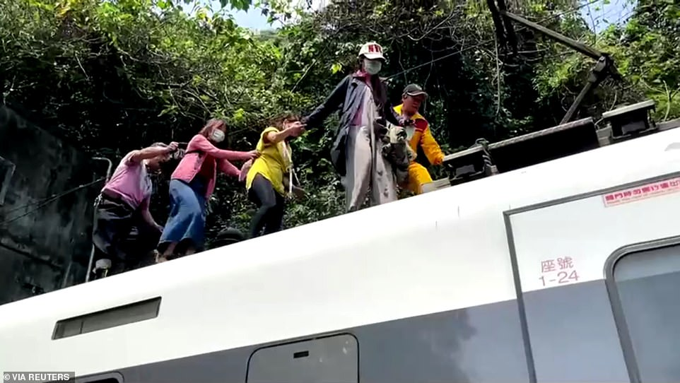 Passengers hold each other as a rescuer guides them over the roof of the train after managing to escape from inside the tunnel