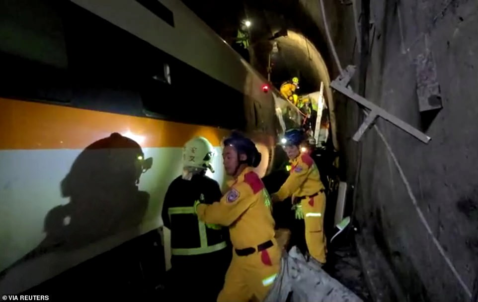 Rescuers rush through the tunnel to try and rescue people trapped inside carriages of the express train