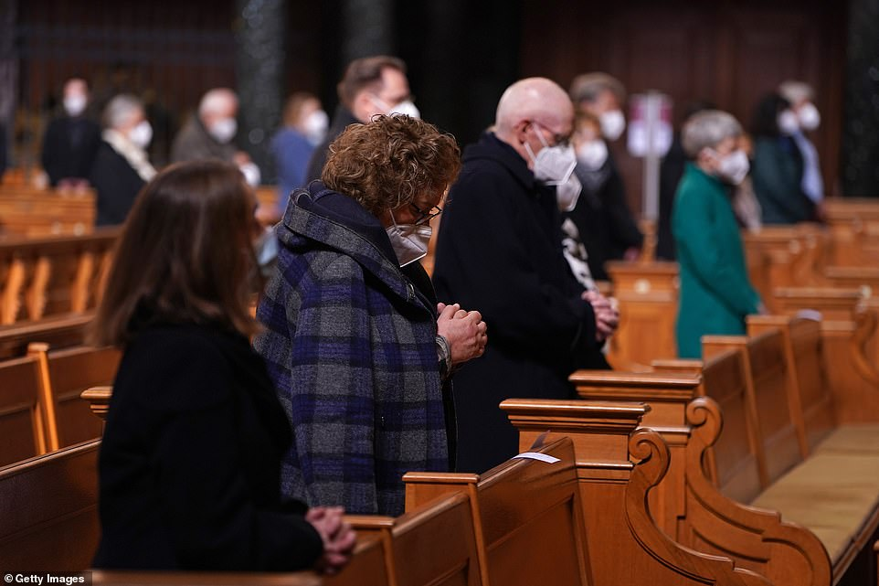 GERMANY: Worshippers wearing masks bow their heads during a service at the Protestant Berlin Cathedral