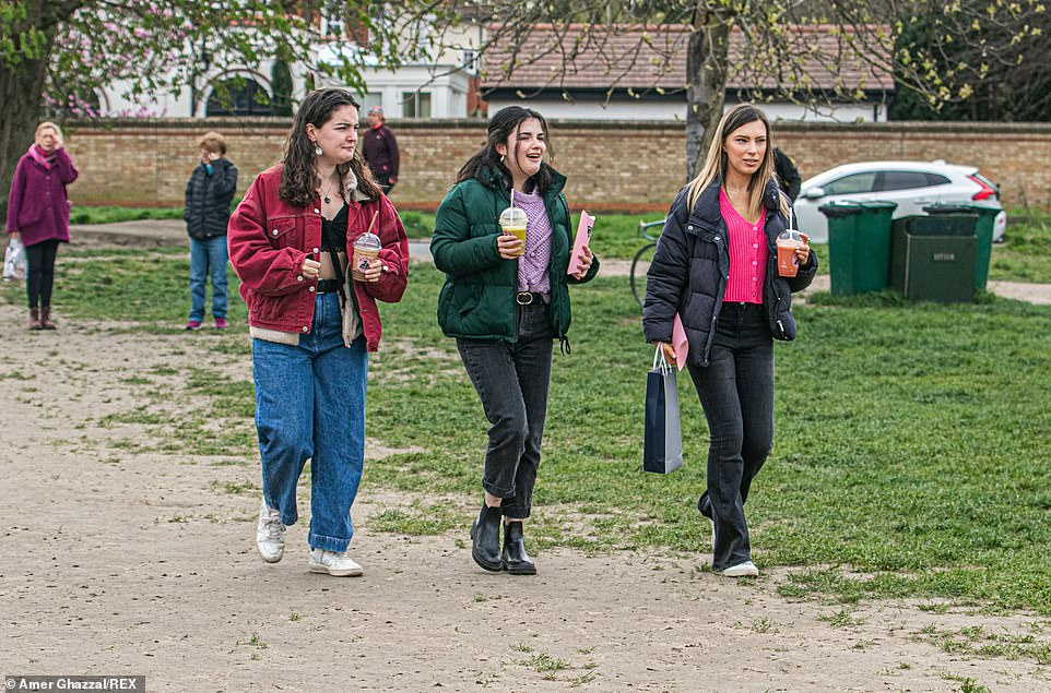 Three girls walking with drinks on an overcast day on Wimbledon Common as lockdown restrictions are lifted