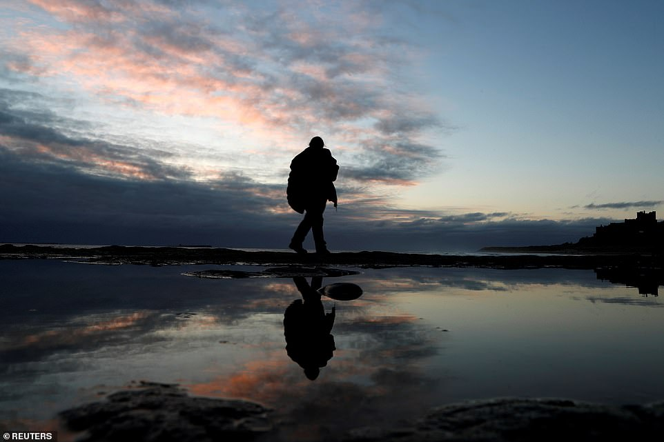 A passer-by walks on Bamburgh Castle beach during sunrise in Northumberland this morning