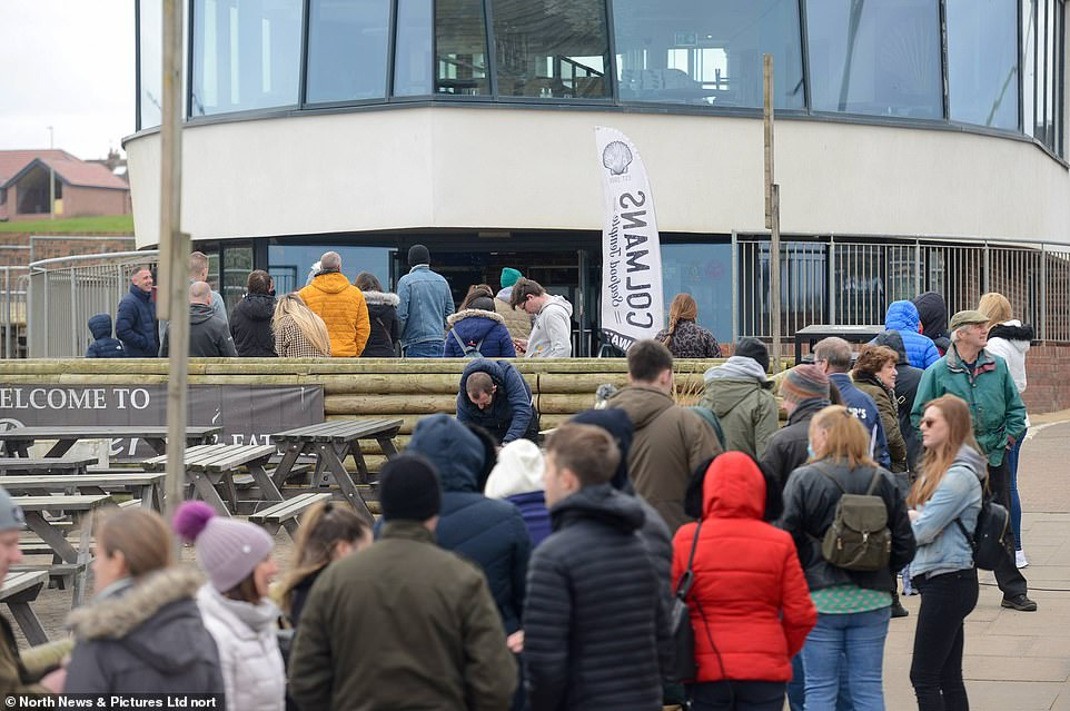 A line of people queue outside Colmans Seafood Temple fish and chips restaurant on South Shields seafront, in South Tyneside
