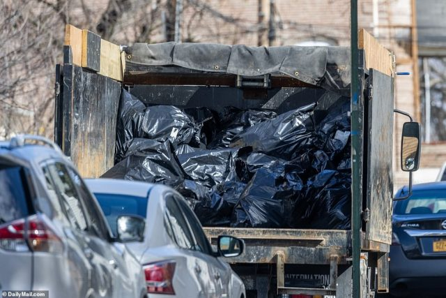 Piles of garbage from Sakash's home are seen on the back of a dump truck on Friday morning as cleaning crews continue to clear out her residence