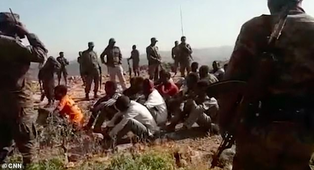 At the beginning of the video, dozens of unarmed men are sat in rows whilst surrounded by the soldiers