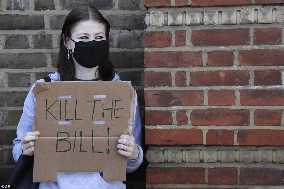 A woman wearing a face mask holds up a cardboard placard during today's protest in Finsbury Park, North London