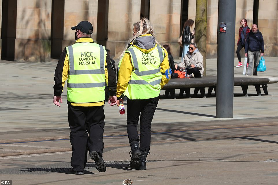 Covid marshals pictured in St Peter's Square, Manchester, as demonstrators take part in a 'Kill the Bill' protest today