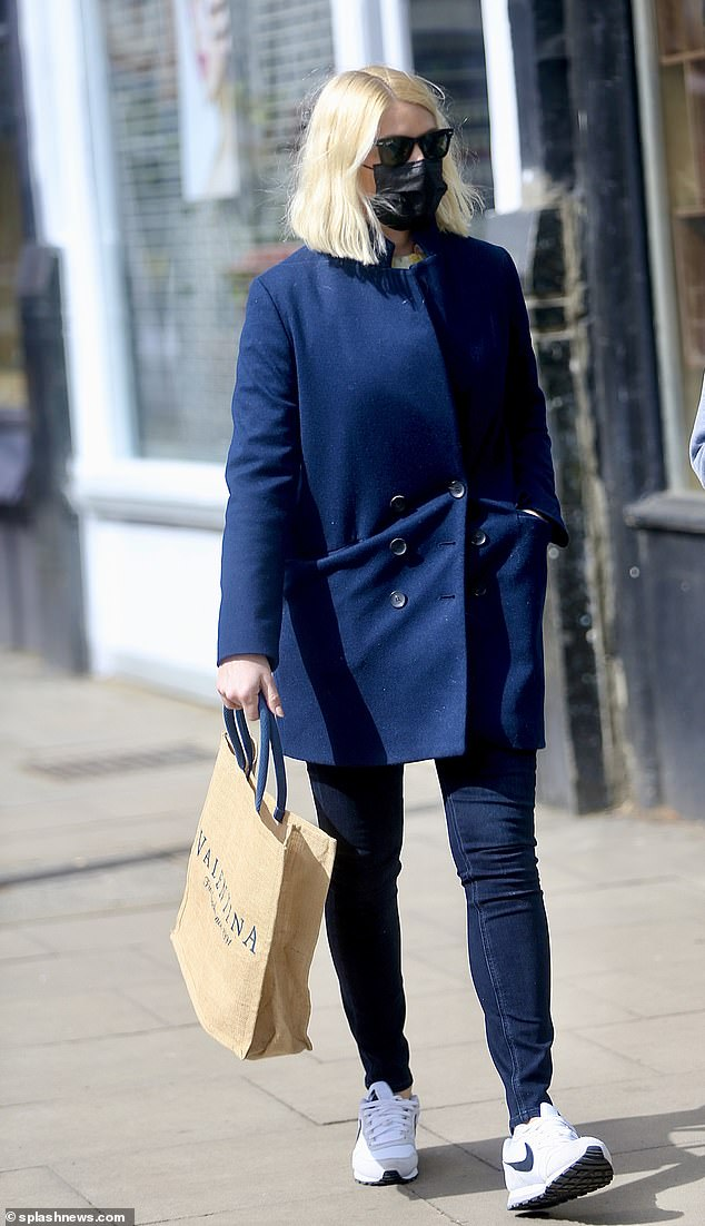 Stylish: On Friday, Holly Willoughby, 40, stepped out in skinny jeans teamed with a chic navy coat for a spot of last-minute Easter weekend shopping in London