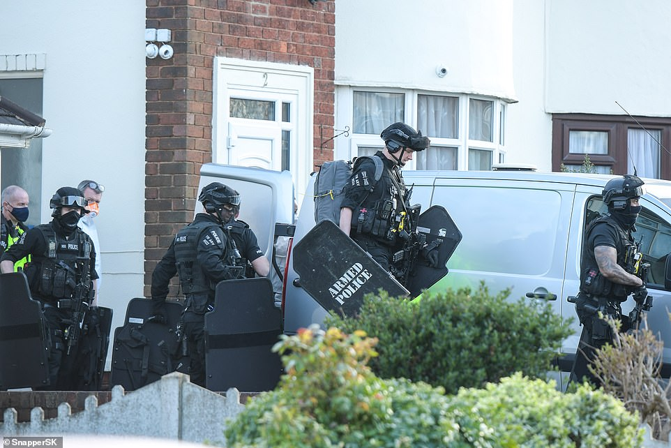 Picutred: Armed officers outside a home in Rowley Regis, West Midlands, where a woman in her 80s was attacked and killed by two escaped dogs. A 43-year-old man has been arrested