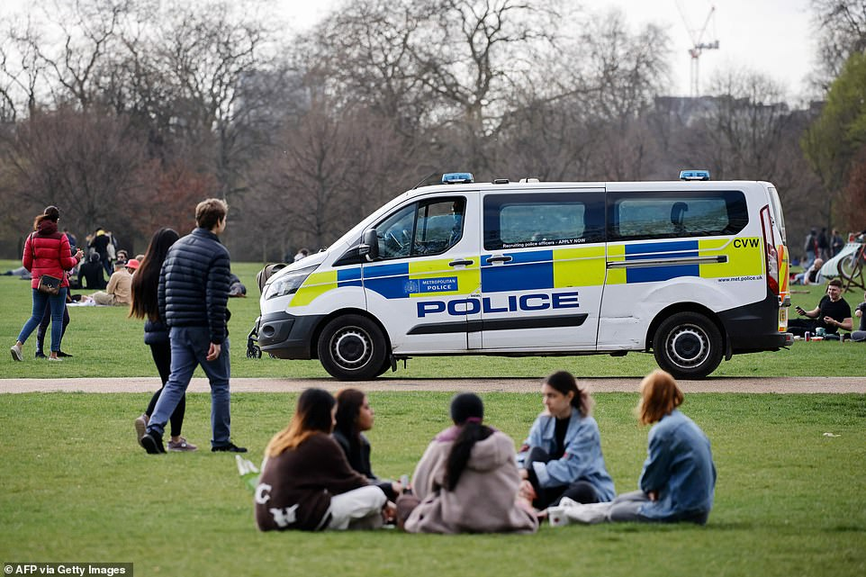 A police van patrols as people relax in Hyde Park in central London this afternoon at the start of the four-day weekend
